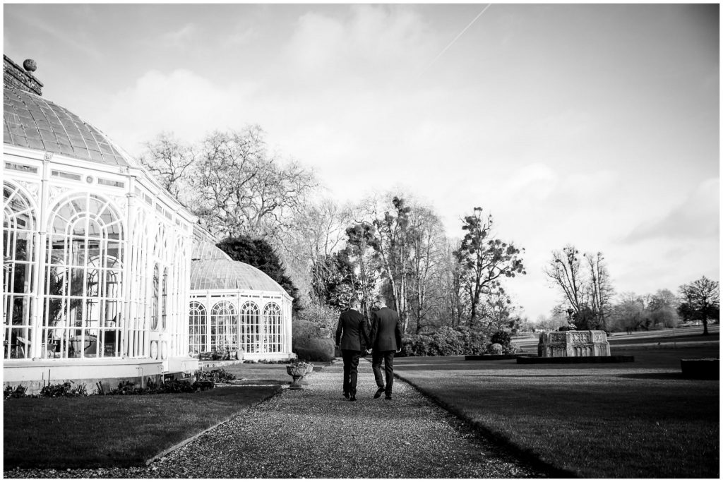 The two grooms walk through the gardens