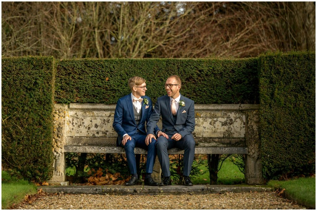Same sex wedding portraits of grooms sat on stone bench in gardens