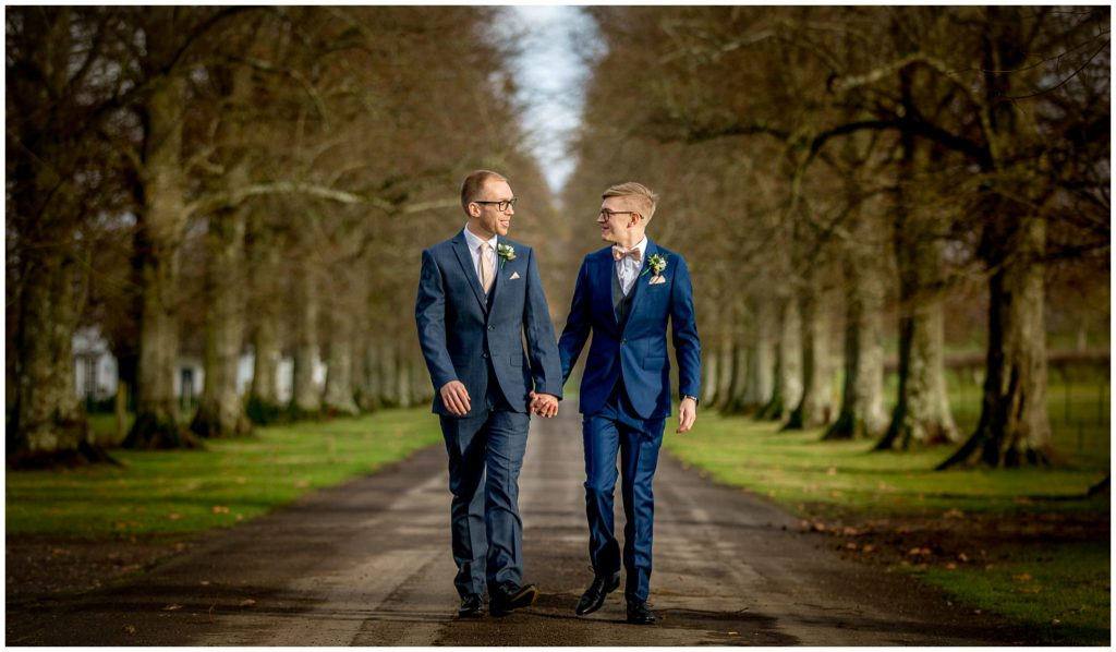 Gay wedding in Winchester, the couple walk along the tree lined avenue towards the mansion house