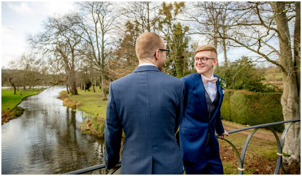 The grooms on the iron bridge with view towards the lake in the background
