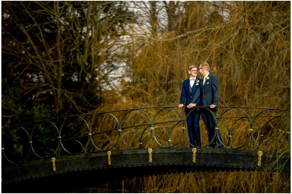 Grooms stood on the iron bridge in Winter light