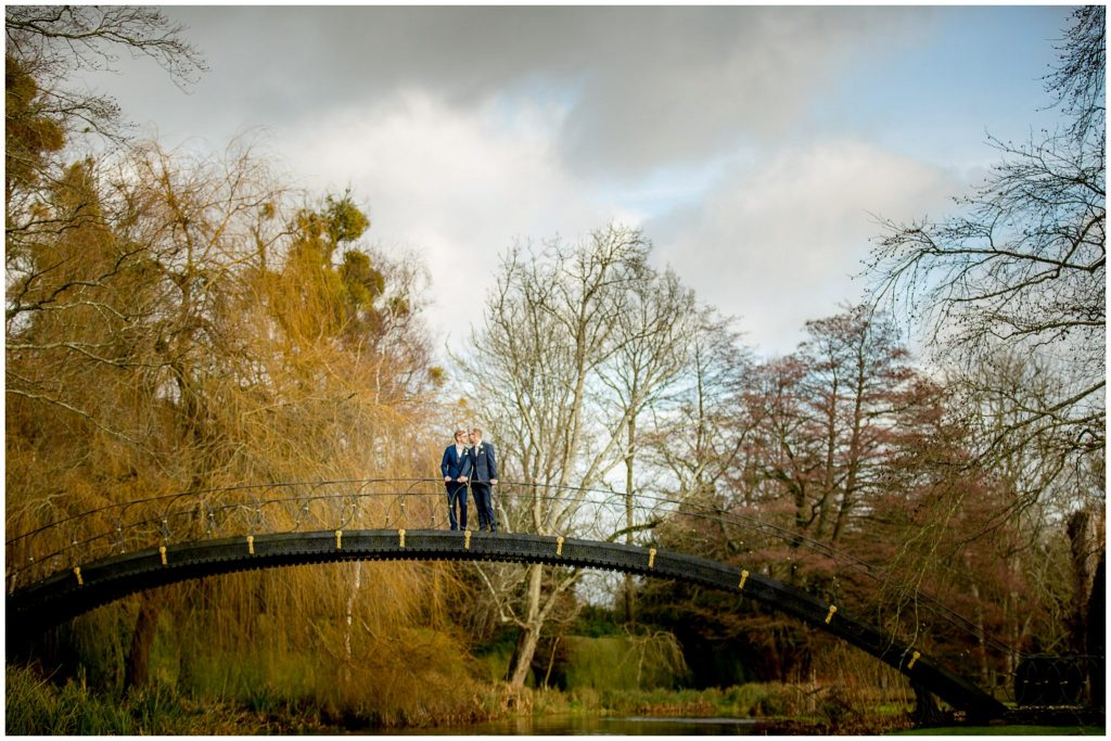 Couple stood on the iron bridge on a beautiful December day before their Christmas wedding