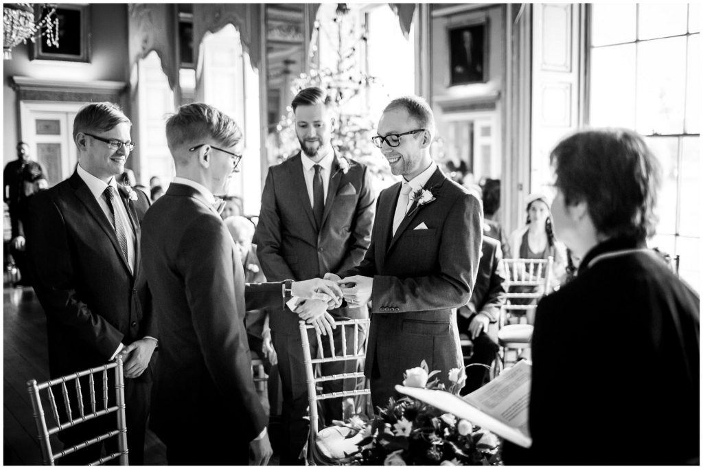 Black and white photo of gay wedding ring exchange in ballroom of manor house near Winchester