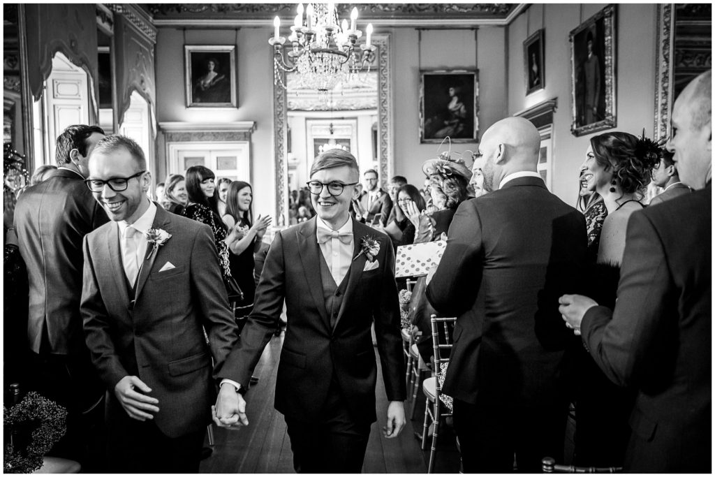 Black and white photo of the grooms walking down the aisle after their wedding