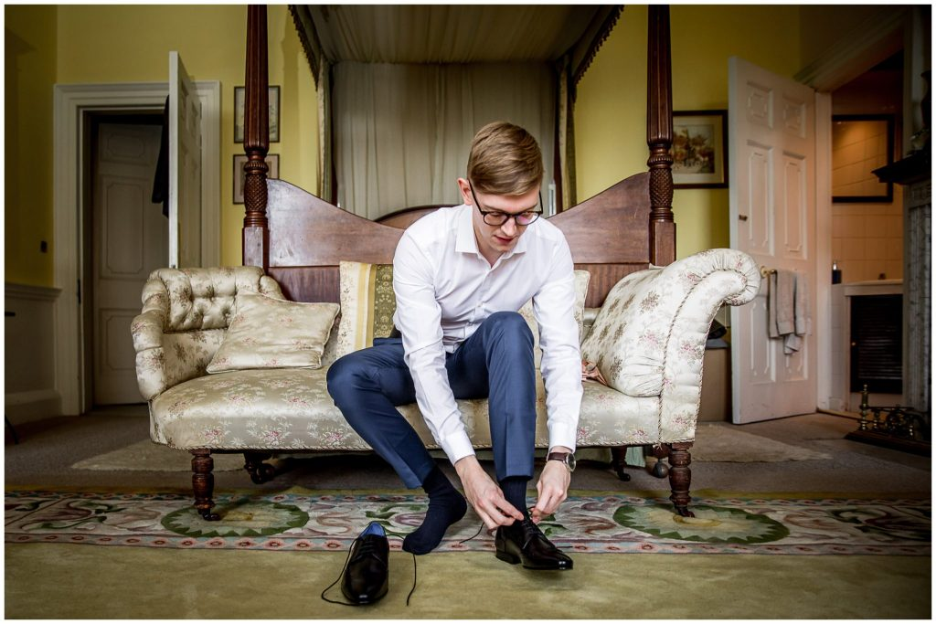 The groom sits by the four poster bed in the dressing room to put on his shoes