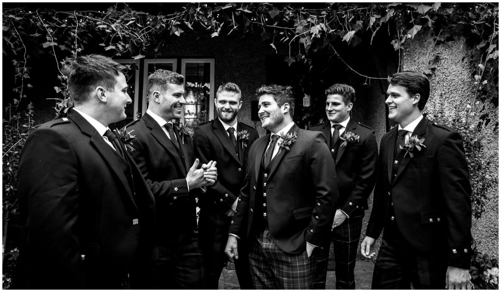 Groom with groomsmen outside house