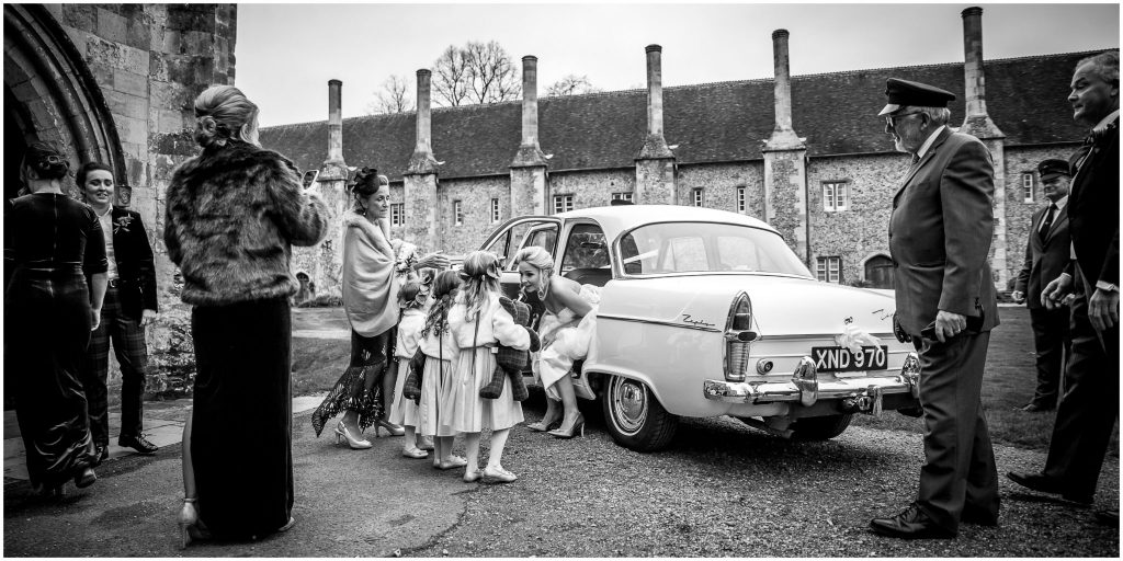 The bride gets out of the wedding car and is greeted by the flower girls
