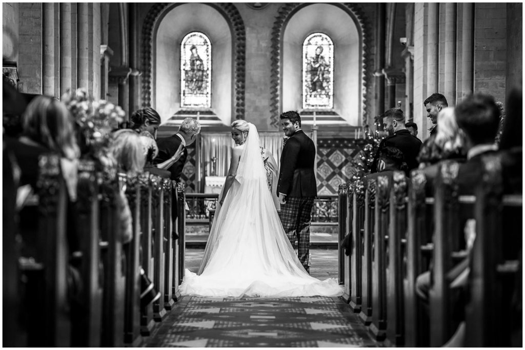 Black and white photo of the couple from the far end of the church