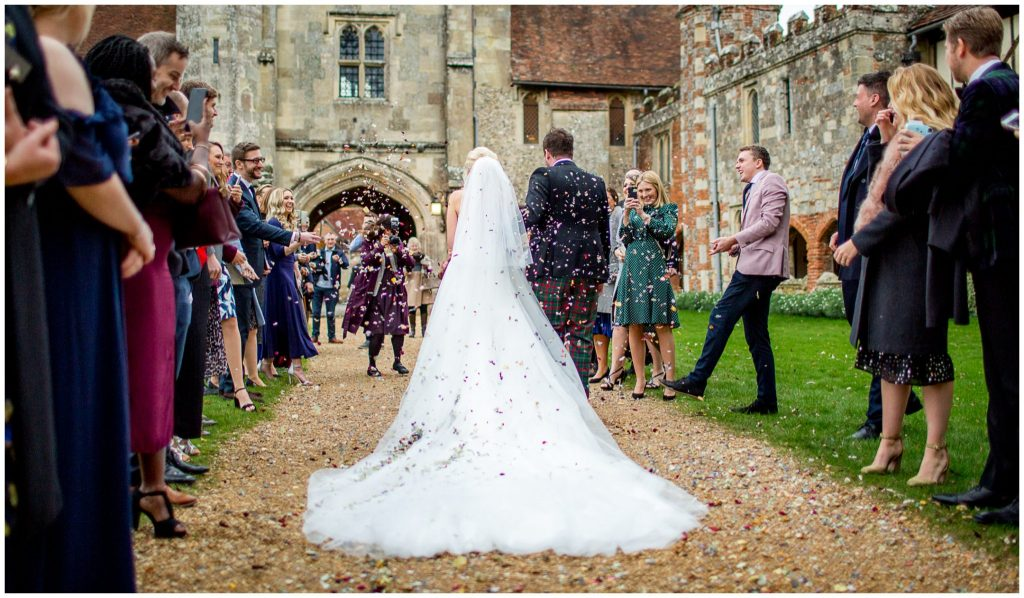 Couple walk through confetti photographed from behind