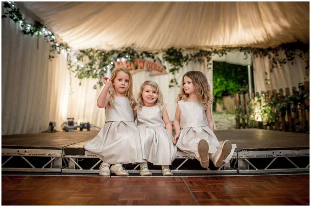 Flower girls sat on the stage at the wedding reception