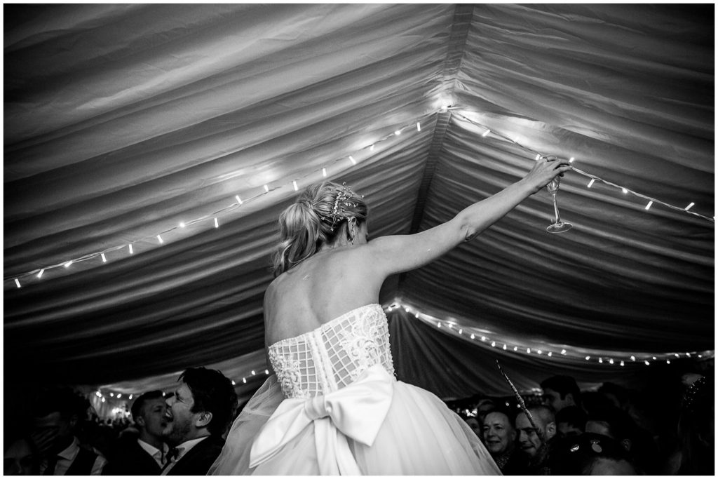Bride on husband's shoulders raising a glass