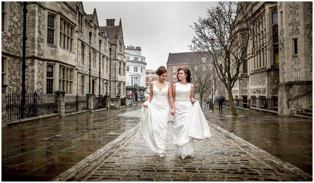 Brides walking holding hands on Castle Hill outside registry office on a rainy day