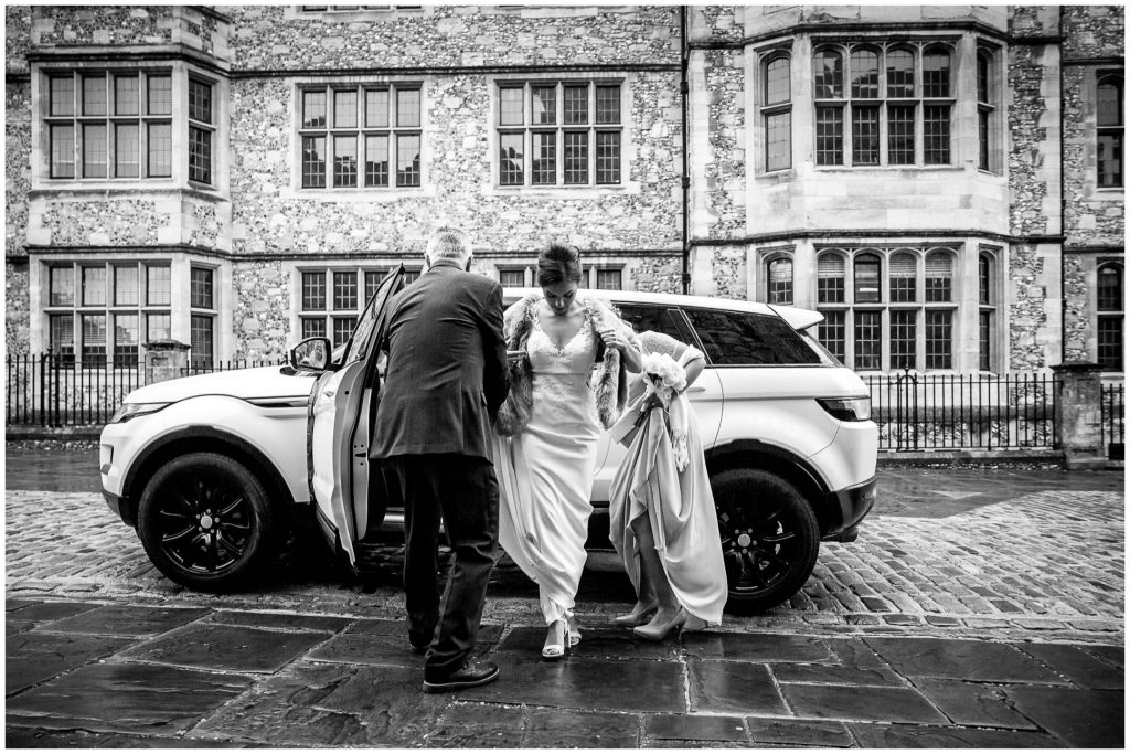 Bride steps out of wedding car outisde the Registry Office
