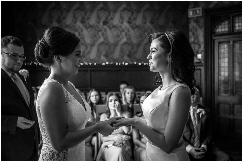Brides holding hands and exchanging wedding rings black and white documentary photo