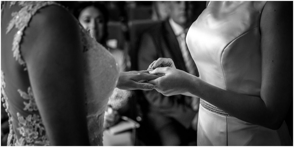 Bride places ring on her bride's finger