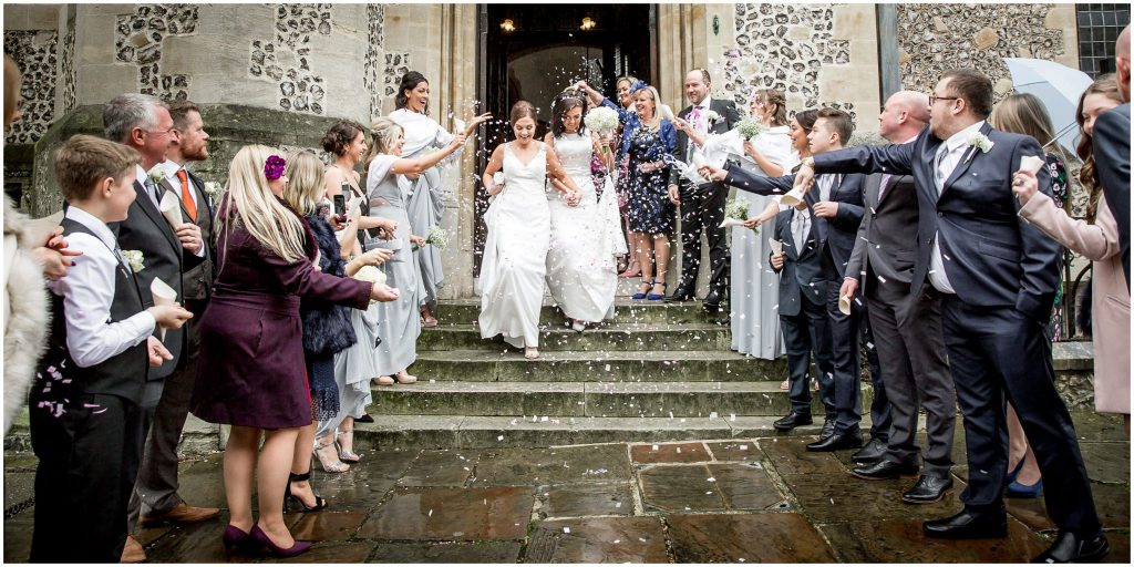 The brides exit the registry office to a shower of confetti
