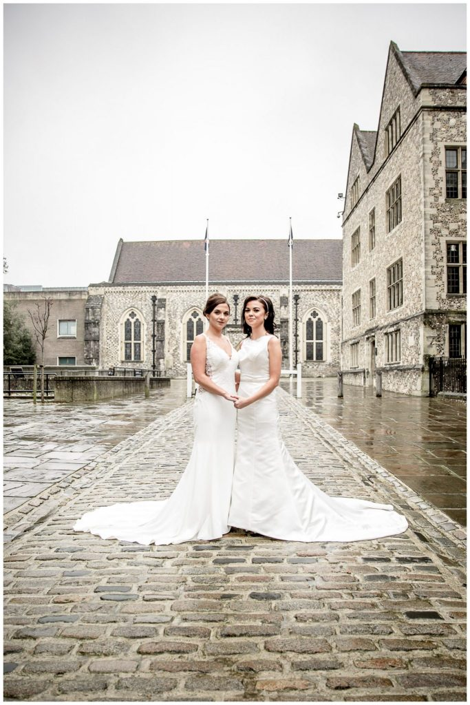 Two brides stood on Castle Hill with the Great Hall in the background