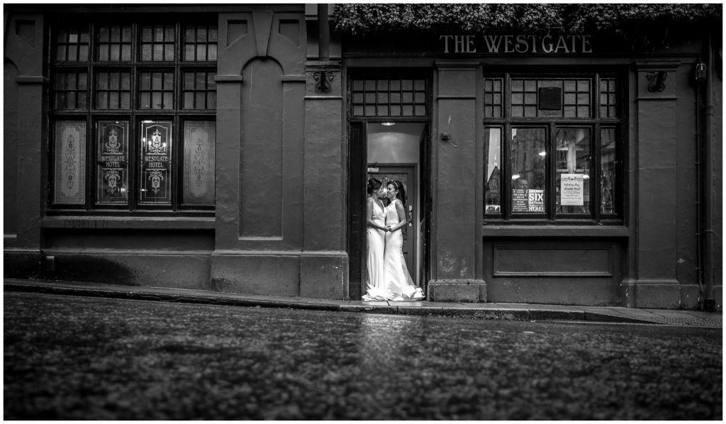 Black and white portrait of brides stood in doorway of Westgate Hotel