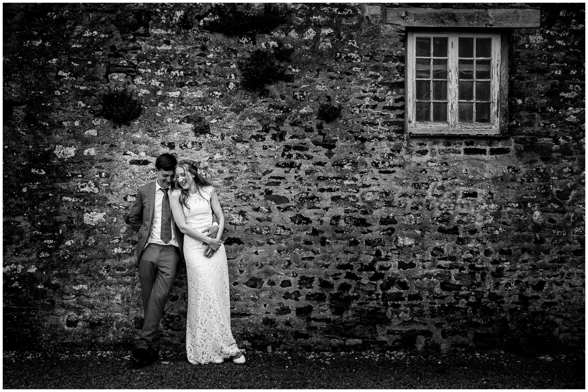 Black and white photo of couple laughing by barn wall
