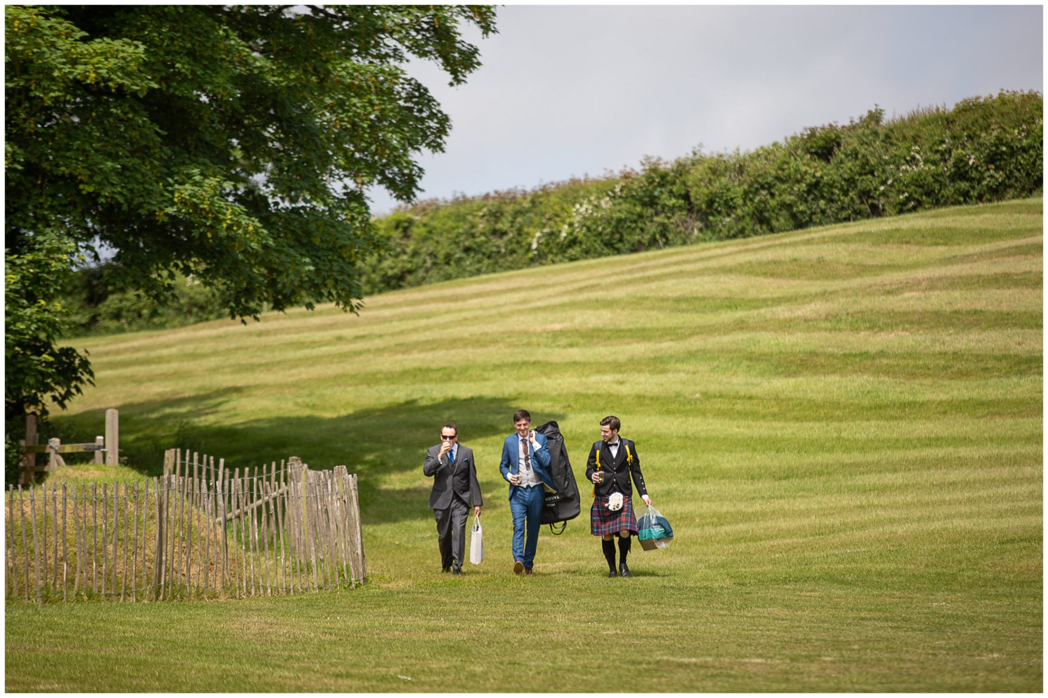 Groom and ushers walk down the hills to the venue in Cornwall