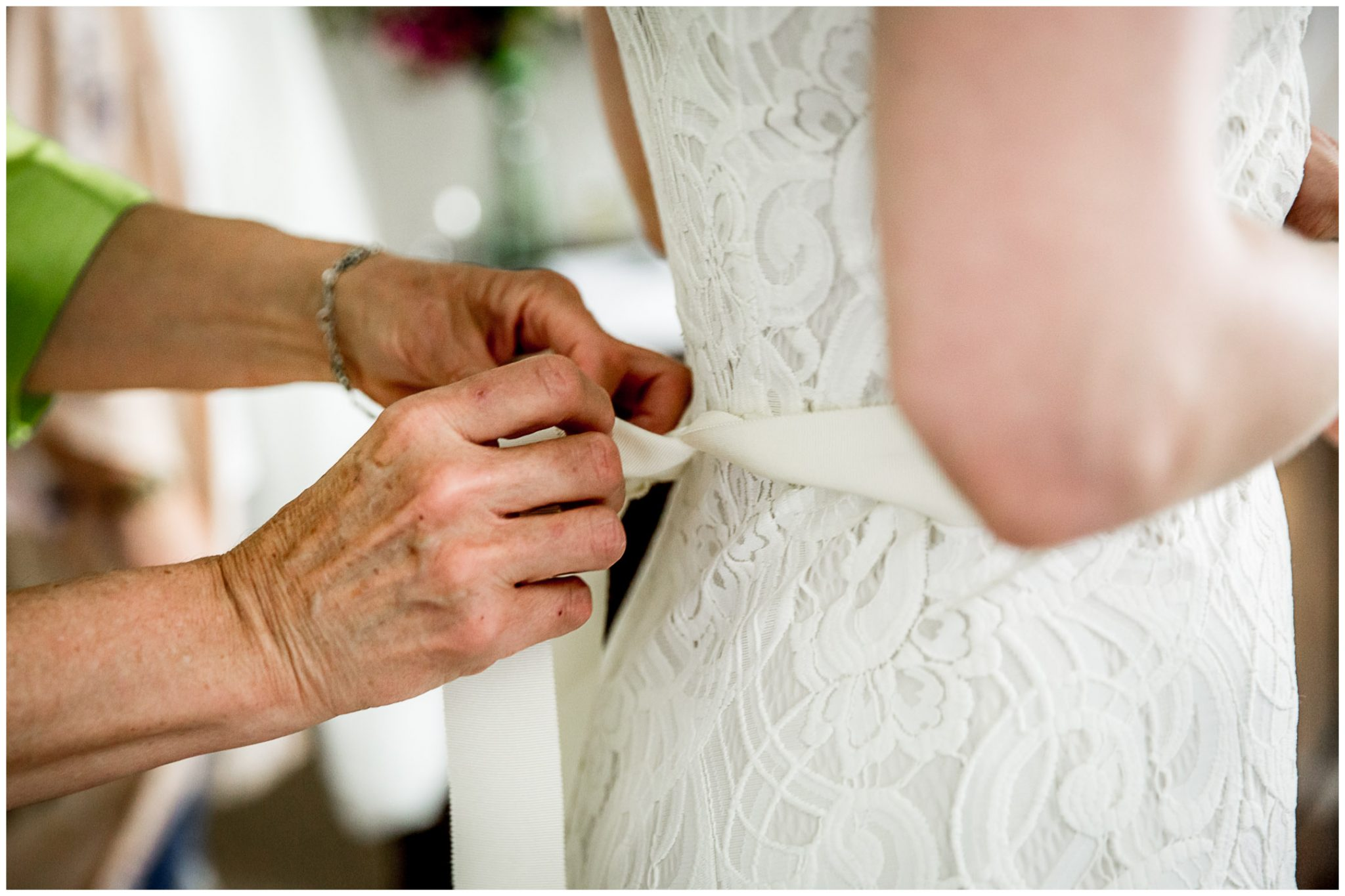 Mother of the bride ties a ribon on the wedding dress