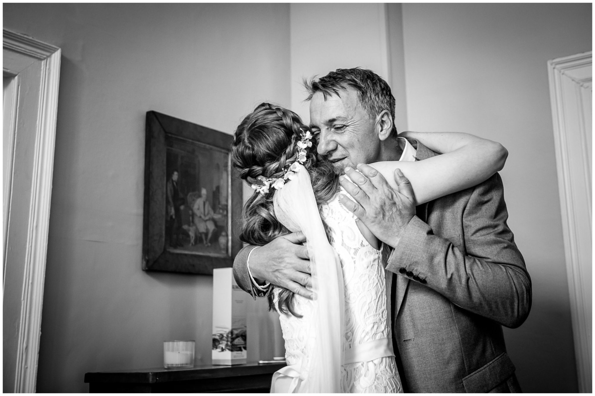 Father of the bride hugs his daughter in wedding dress