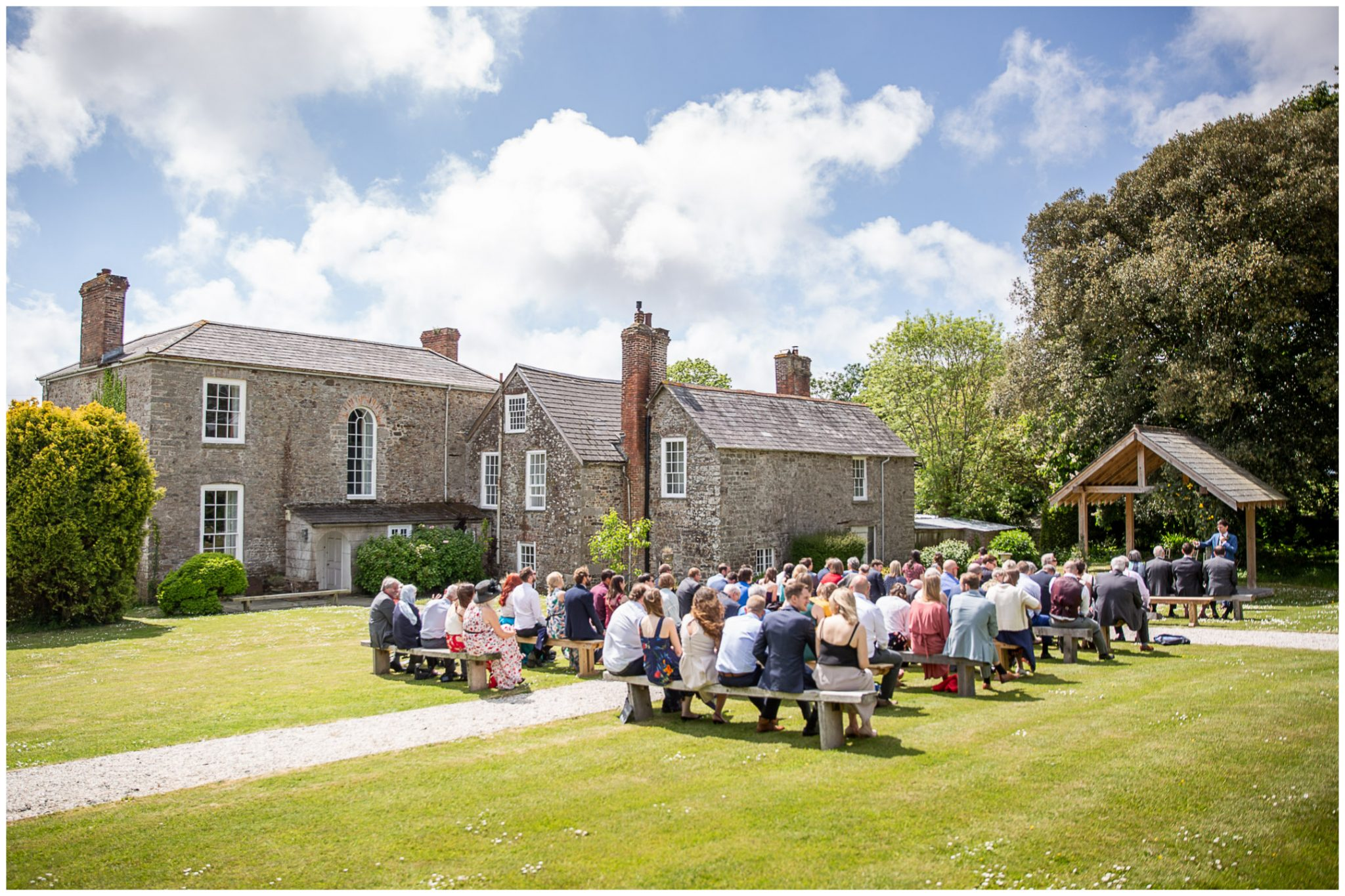 Outdoor ceremony seating in gardens of farmhouse on sunny day