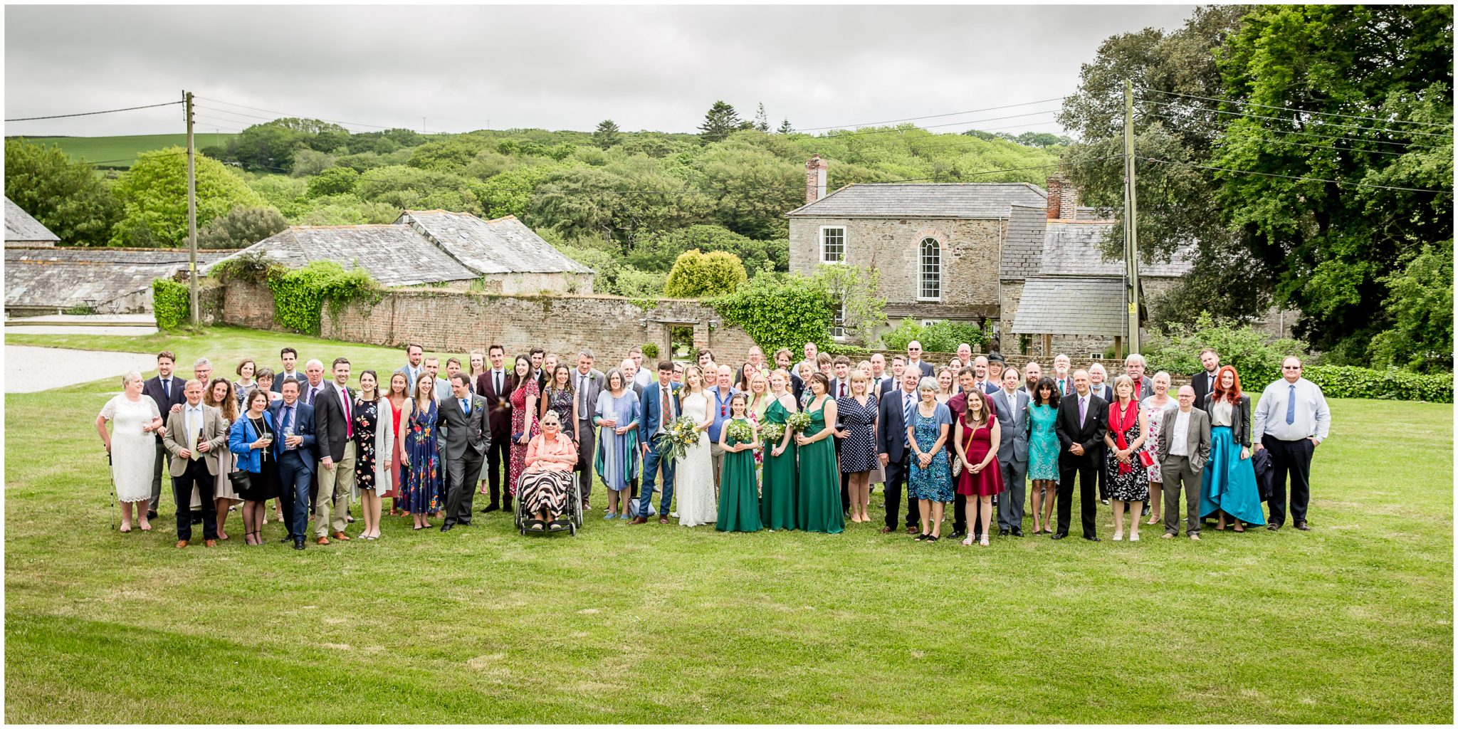 Group photo of all guests with house and hills in the background