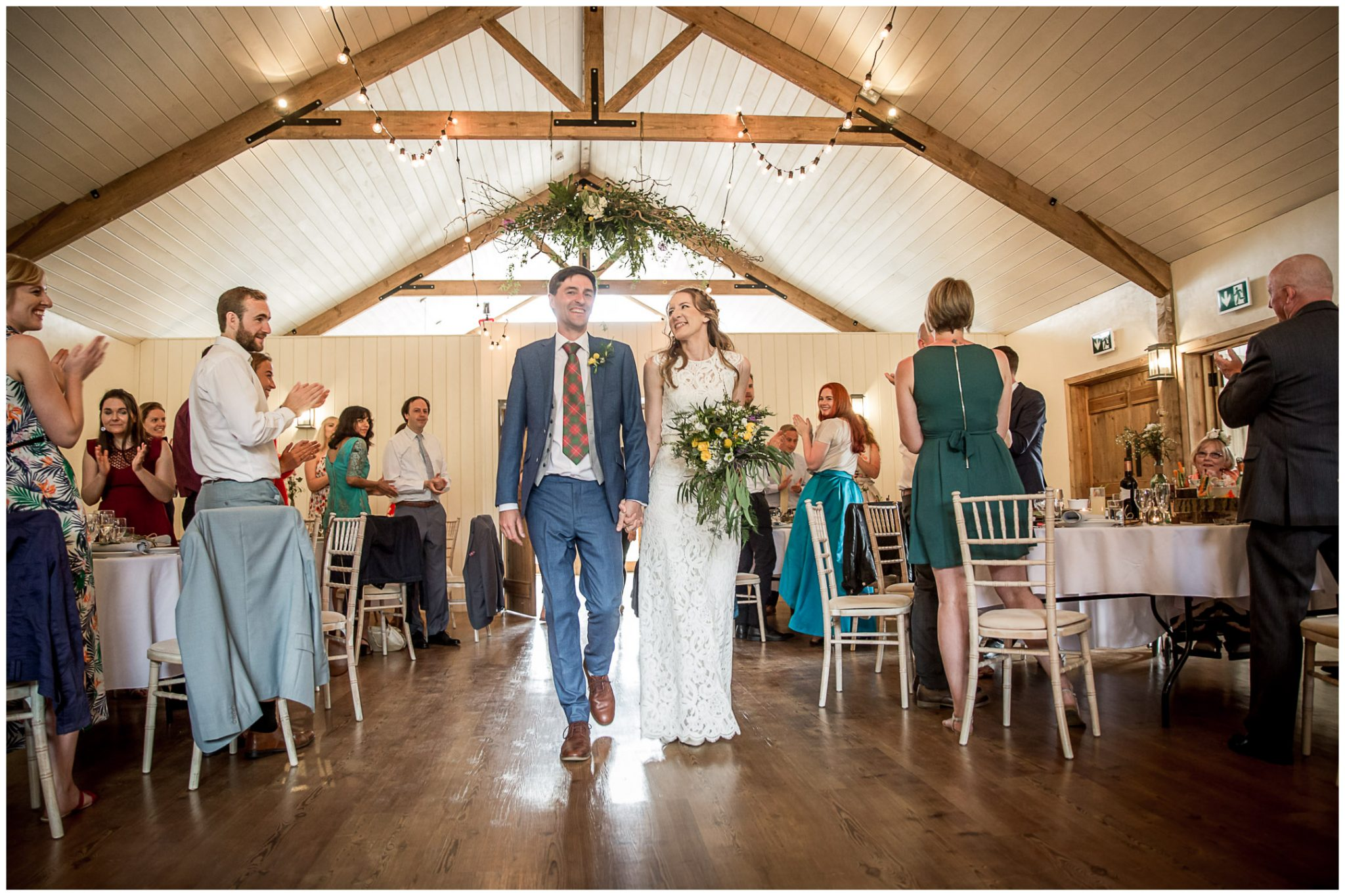 Bride and groom enter the barn reception space for their wedding breakfast