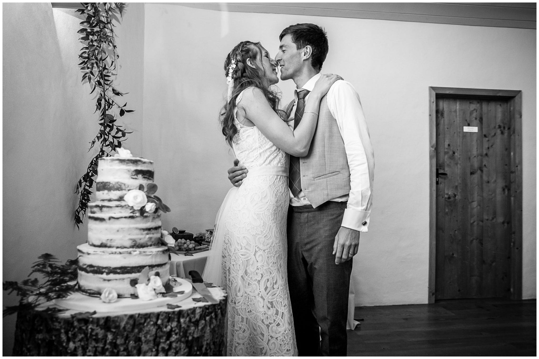 The couple kiss during the cutting of the cake