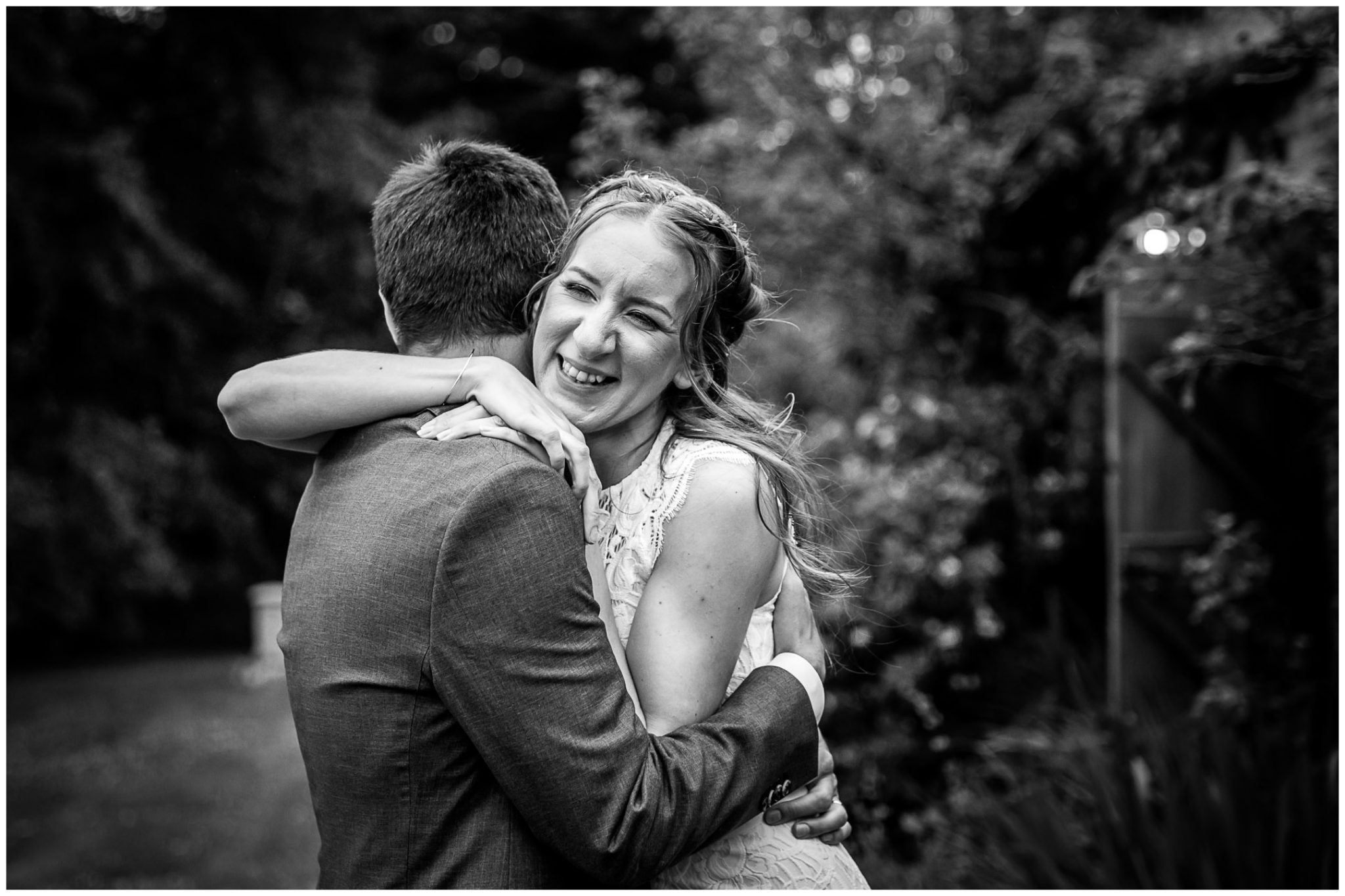 Bride and groom hugging black and white portrait
