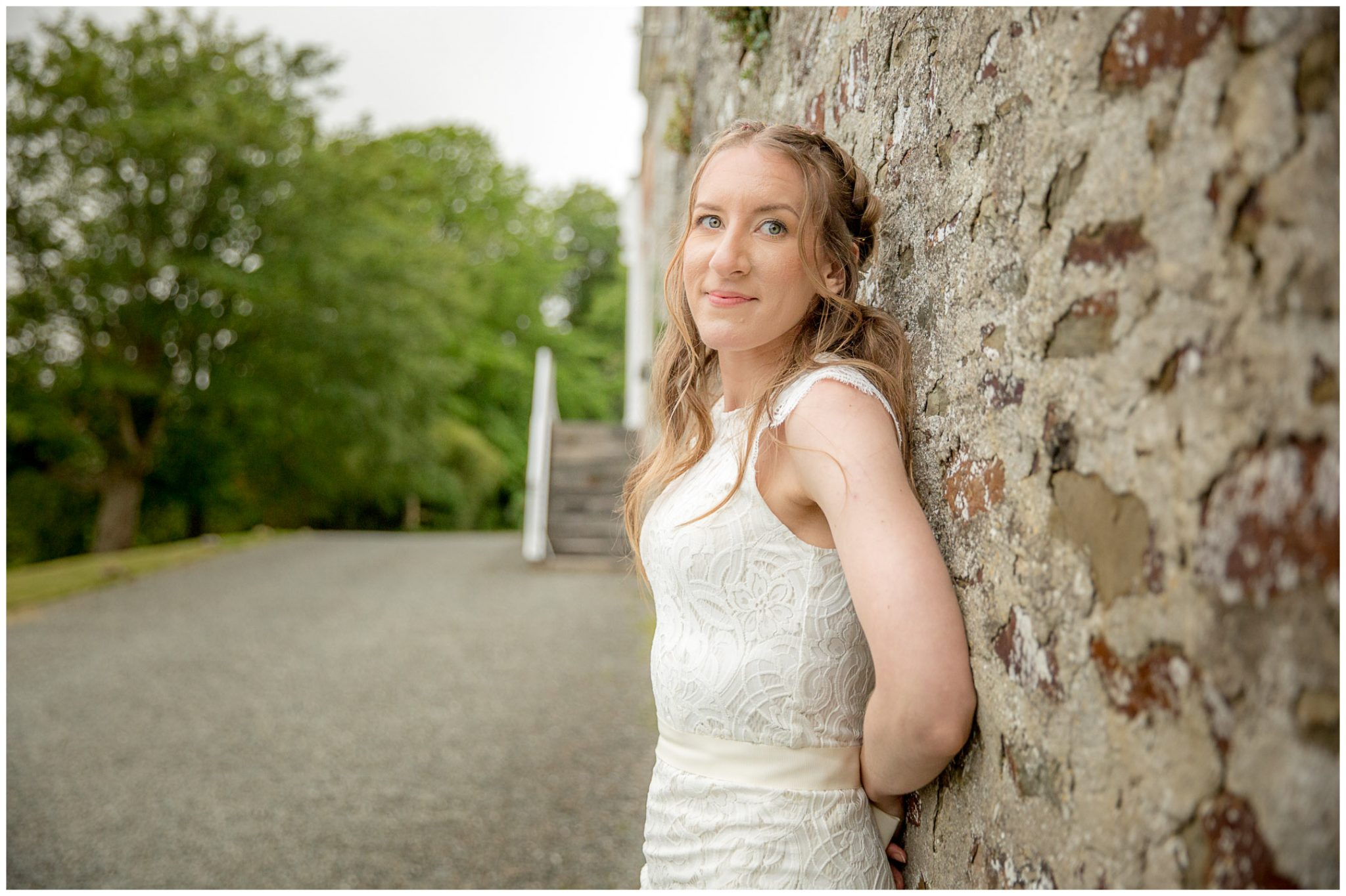 Bride portrait leaning against stone wall