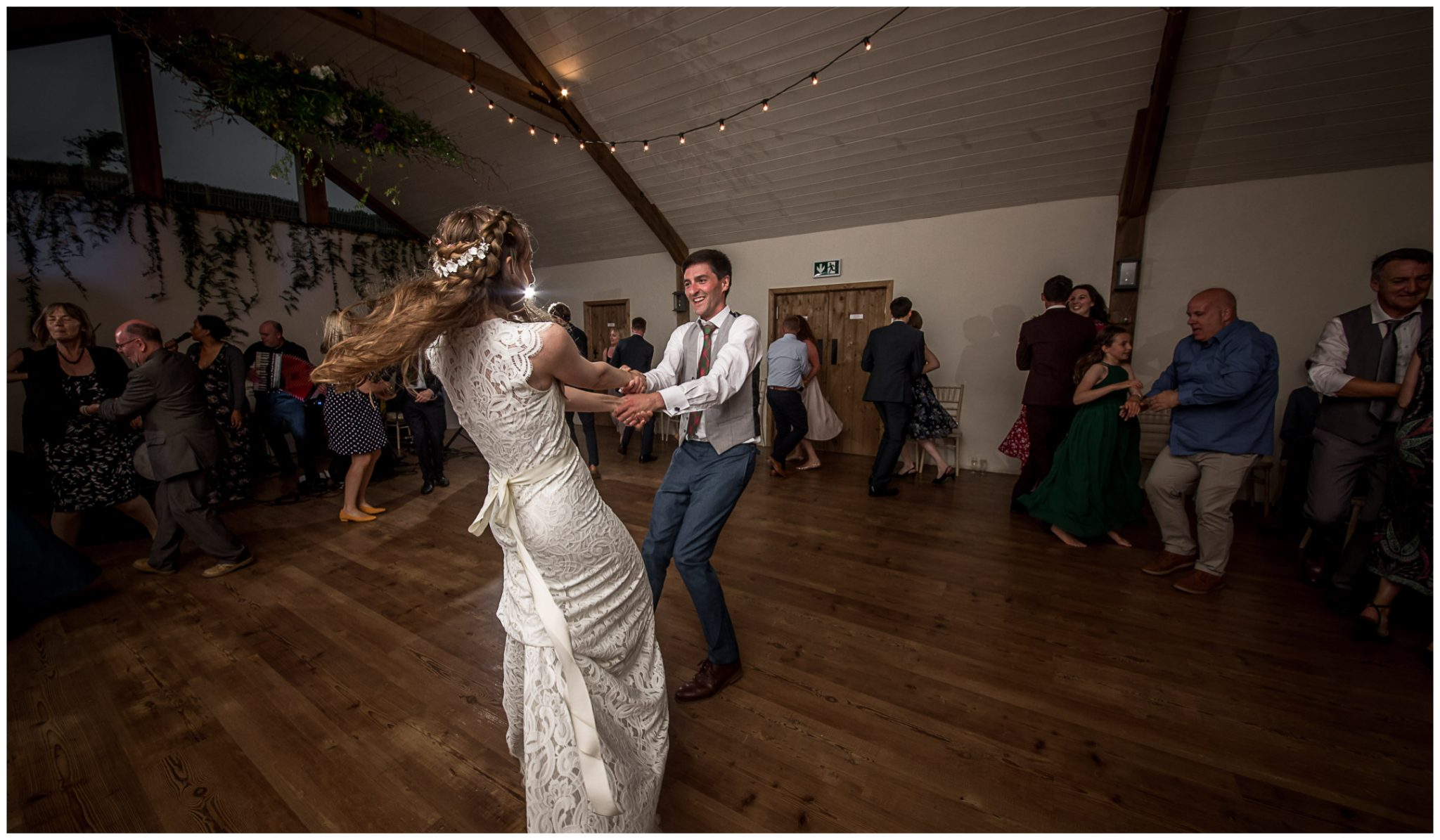 The groom swings the bride around during their dance