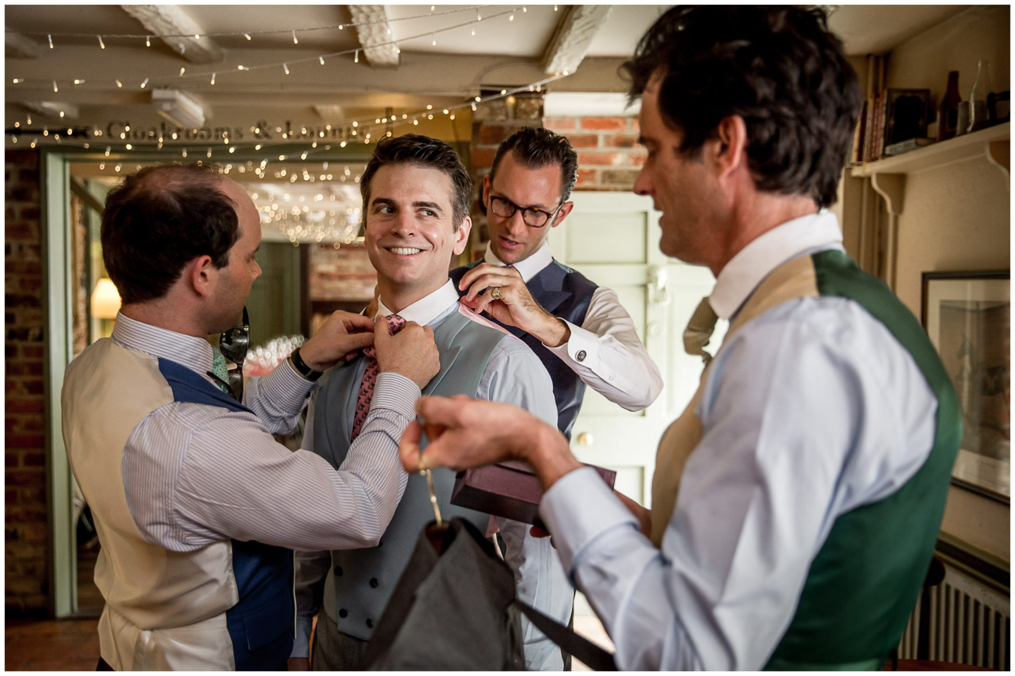 Best man and yshers help the groom to get ready for the wedding