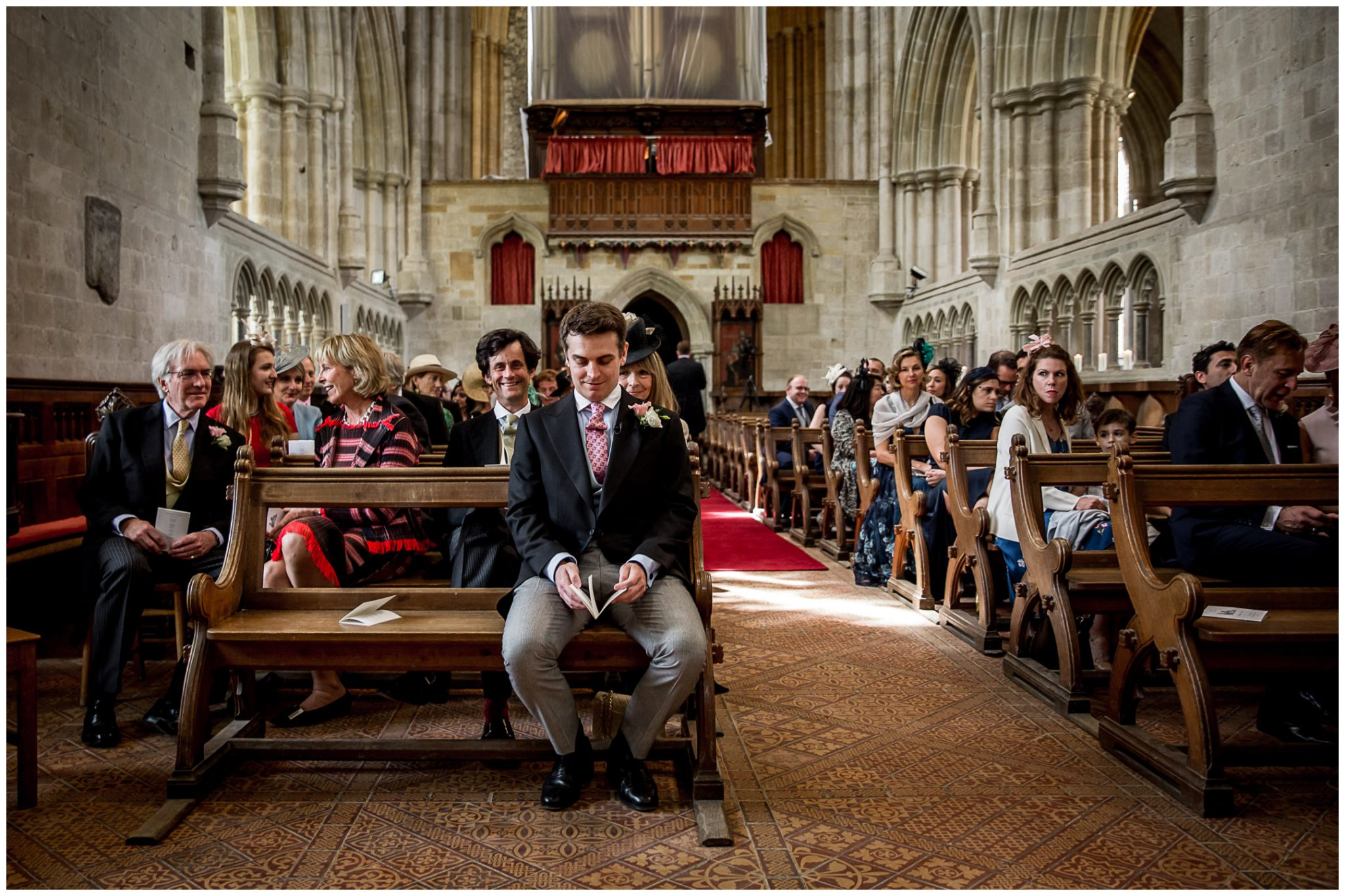 The groom sits alone at the front of the church waiting for his bride to arrive
