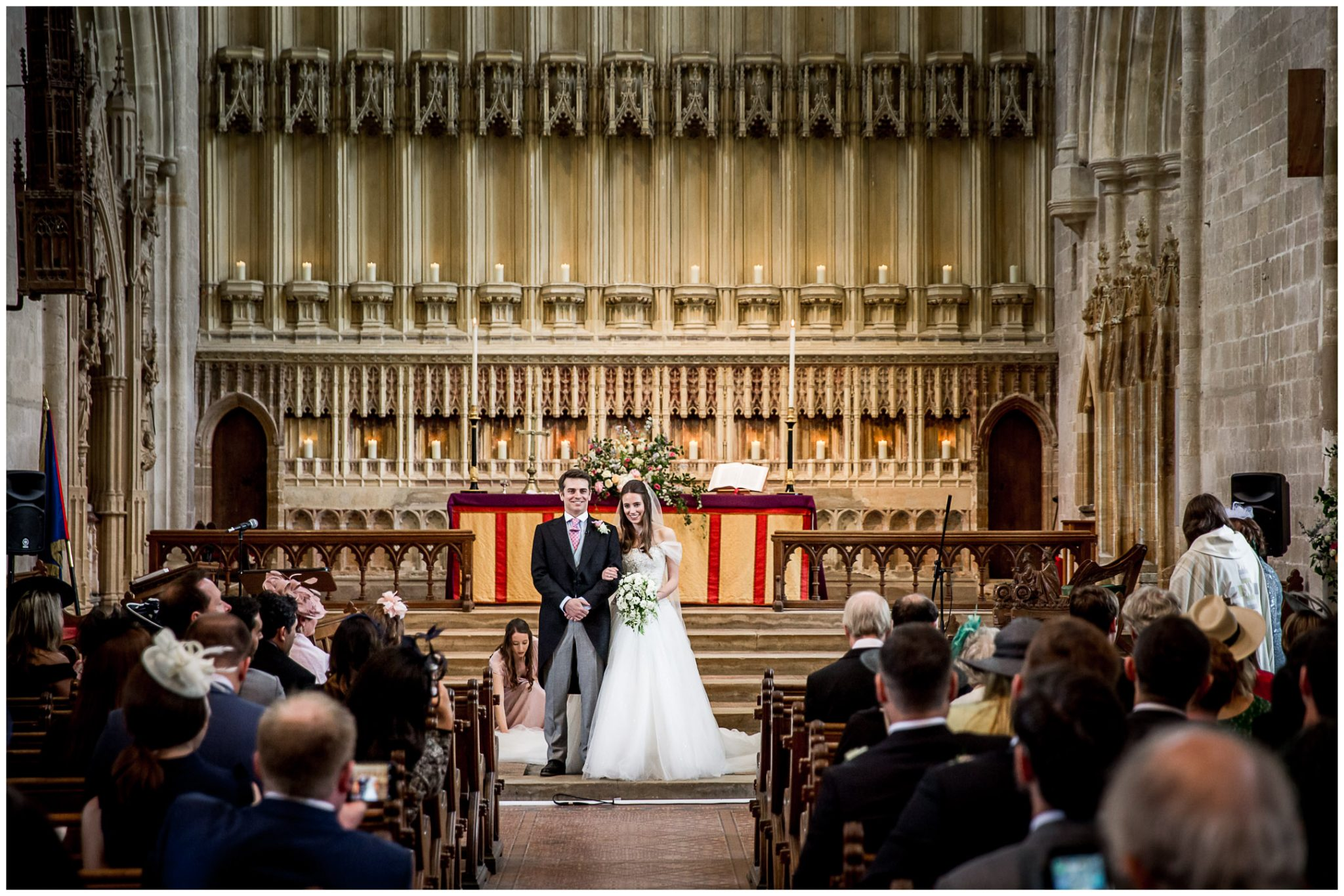 The couple stand together at the front of the church after their wedding