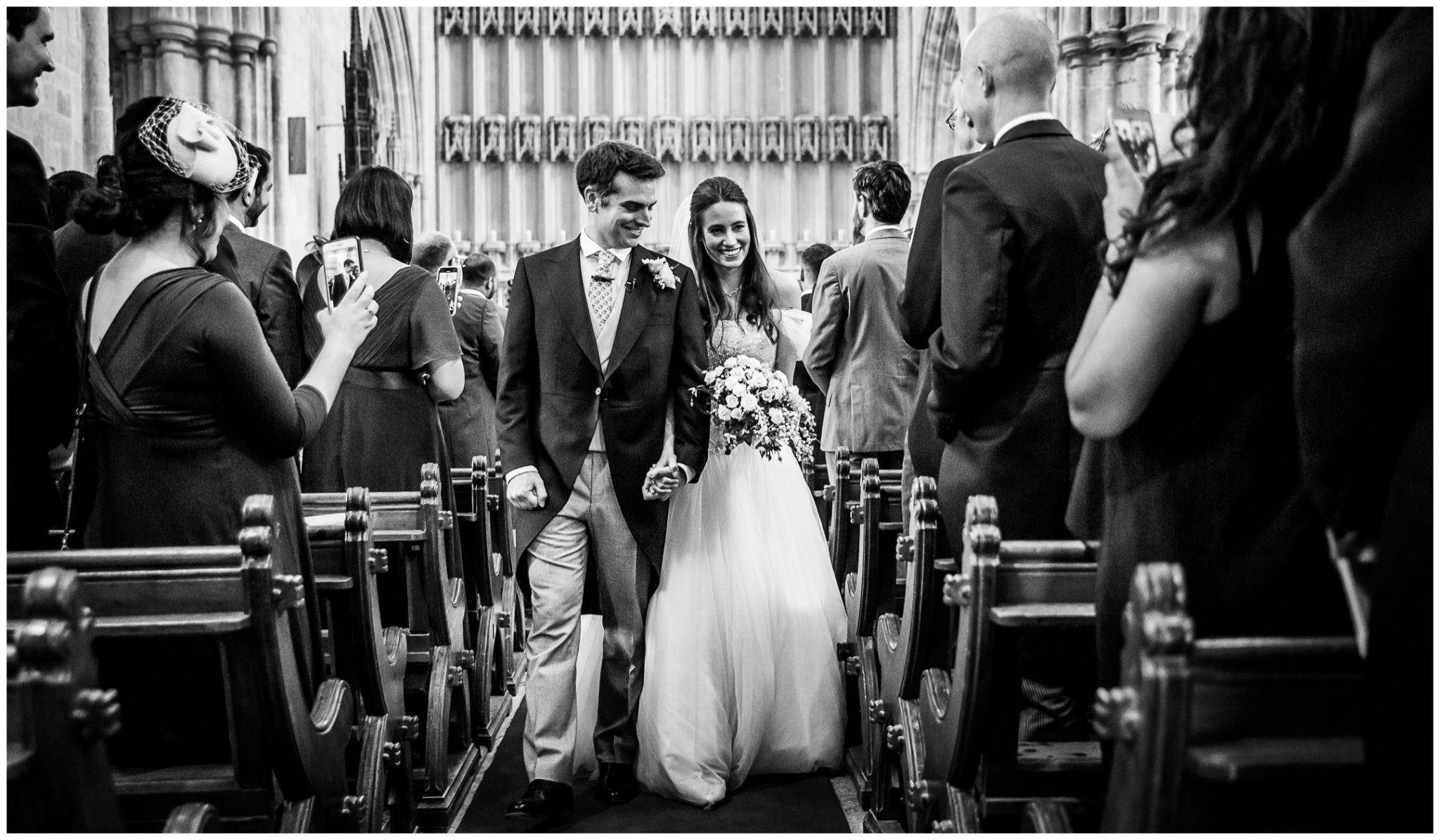 Black and white photo of the couple walking down the aisle