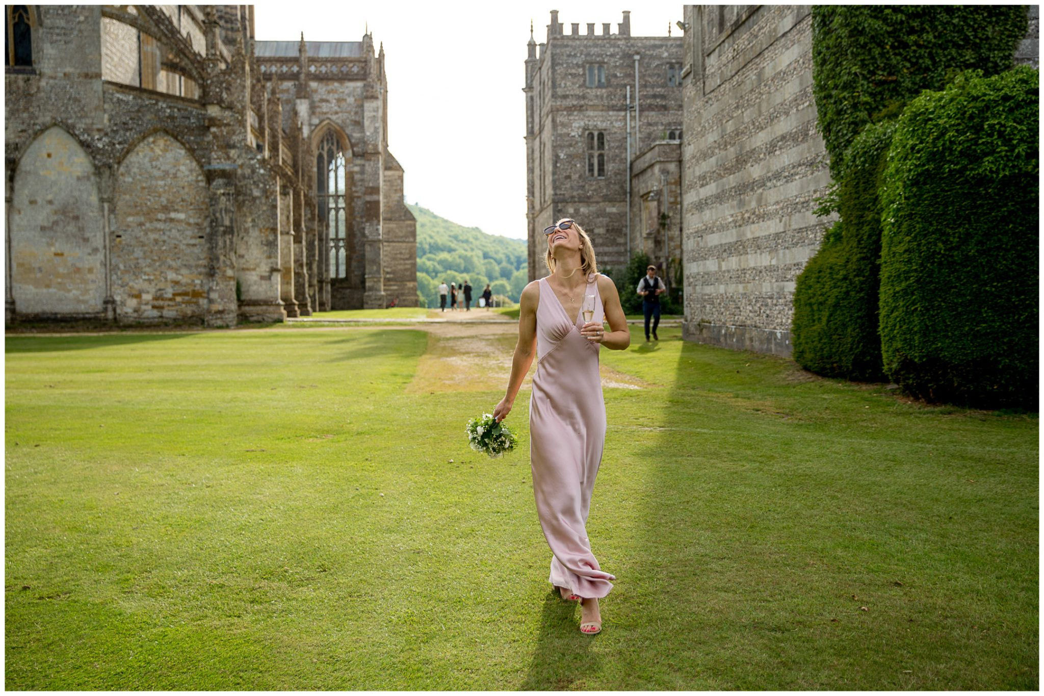 A bridemsiad walks through the school and Abbey grounds in the summer sunshine