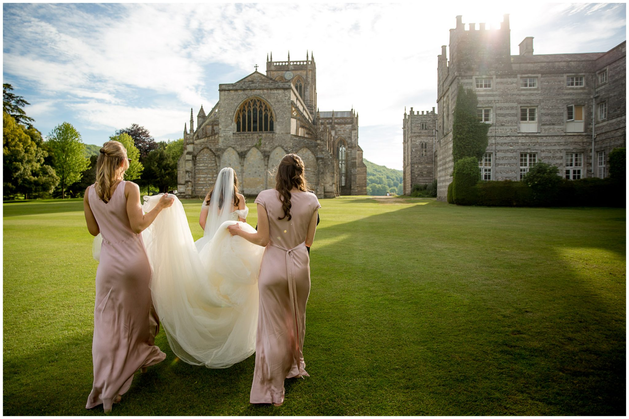 Bridesmaids help to carry the train of the bride's wedding dress