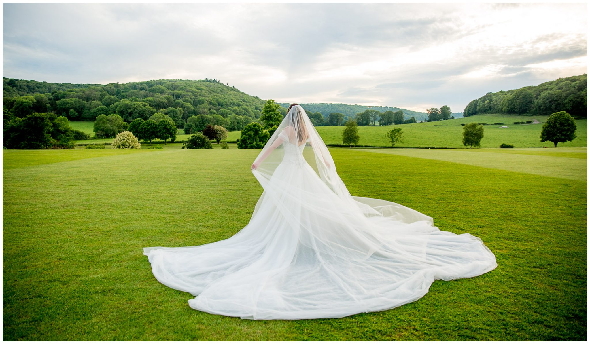 The bride's dress fanned out as she walks across the lawn