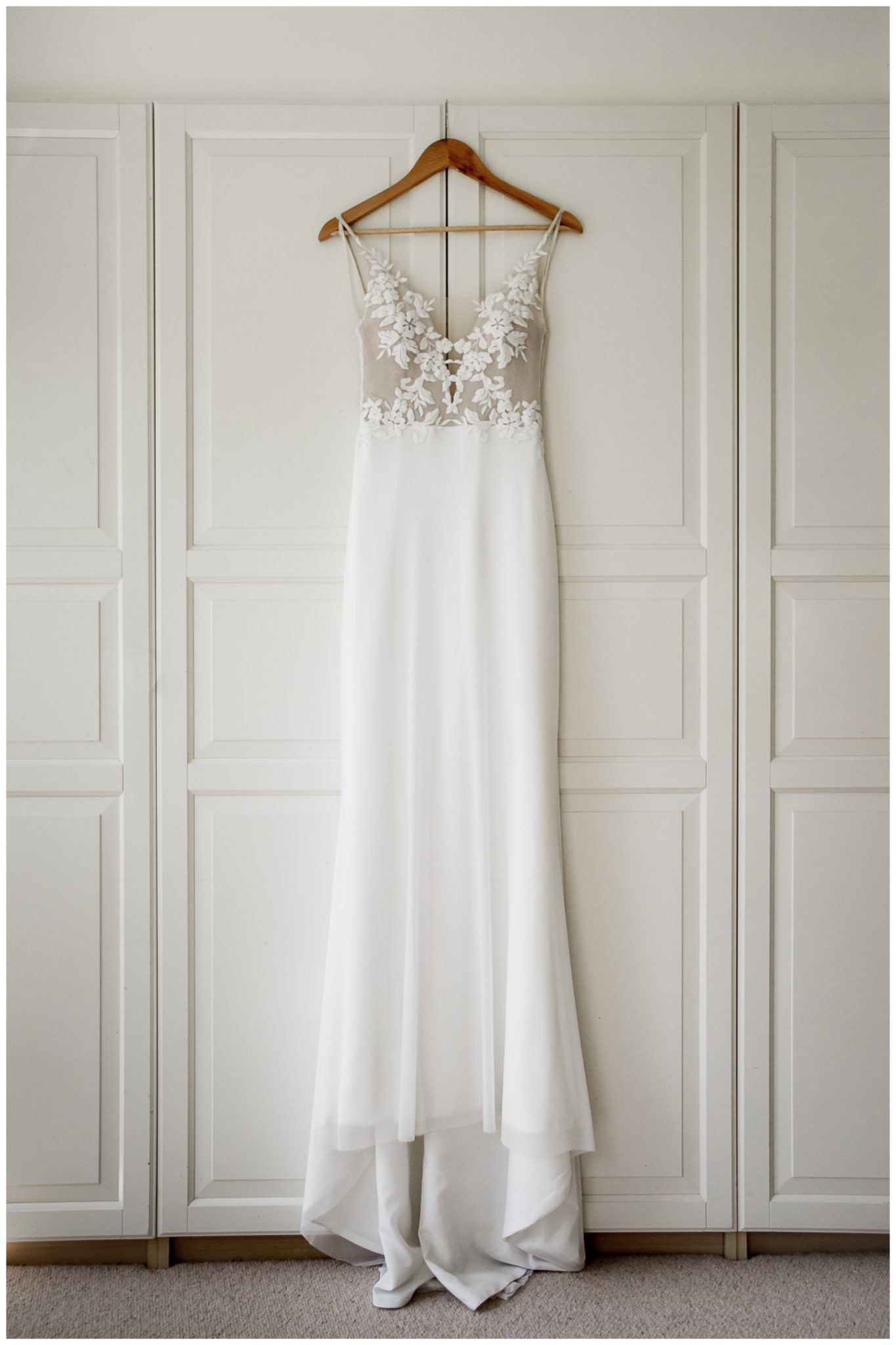 An elegant wedding dress hangs in the bedroom