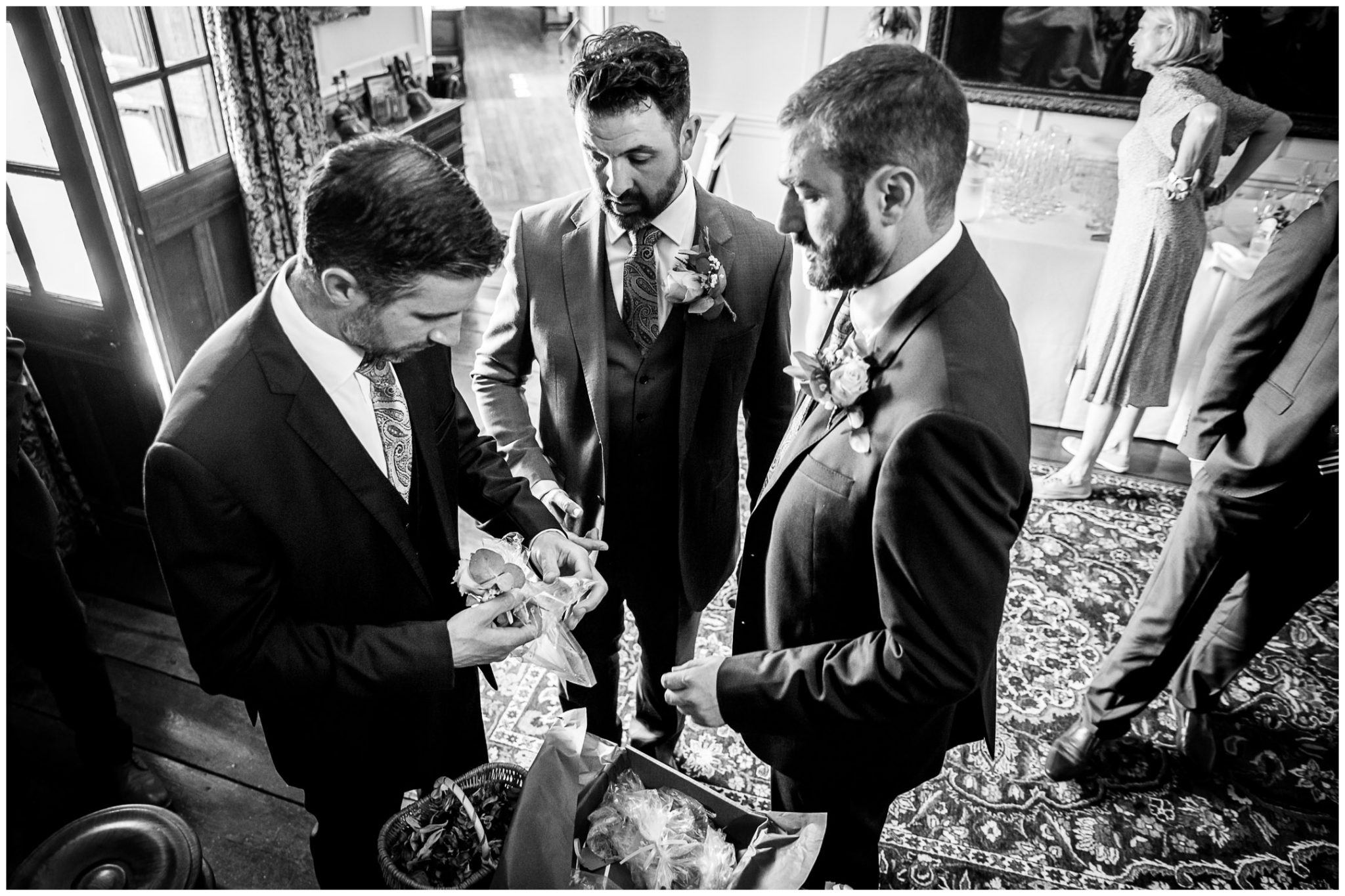 The groom and best men work out what to do with buttonholes