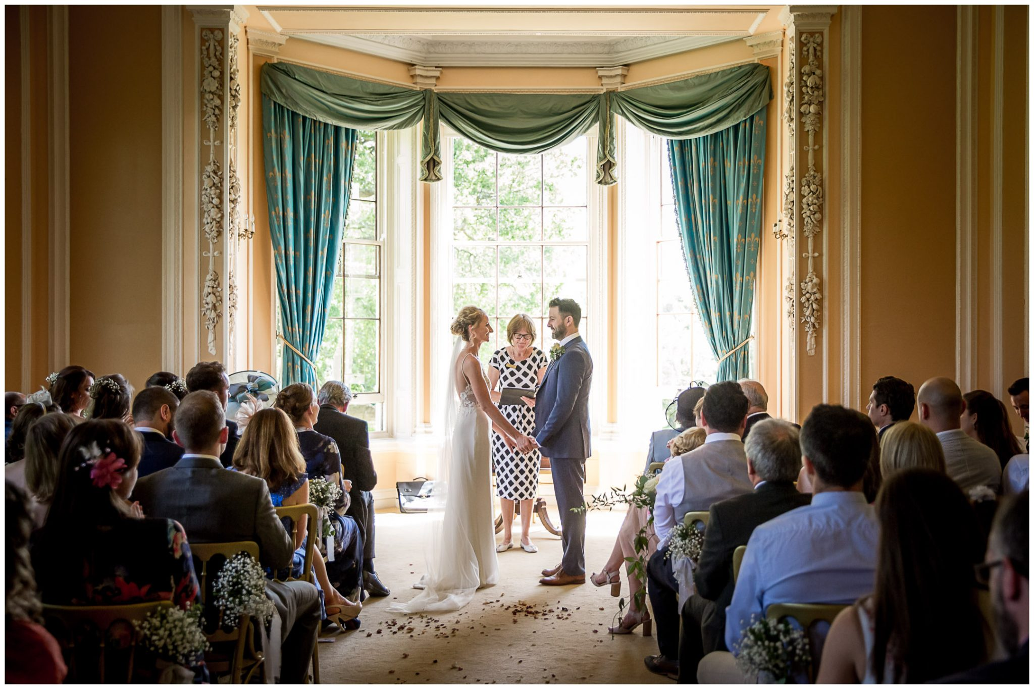 The couple turn to face each other in front of the big bay window of the ceremony room at Newhouse Estate New Forest wedding venue