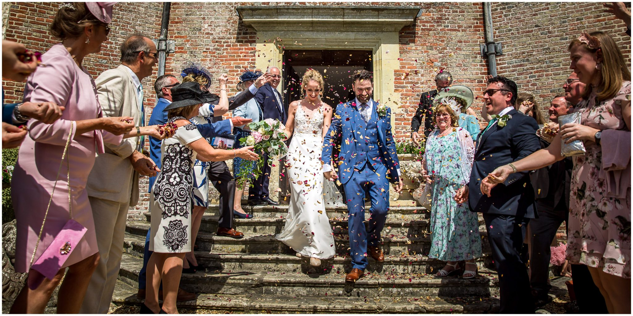 Bride and groom emerge from the house to a shower of confetti