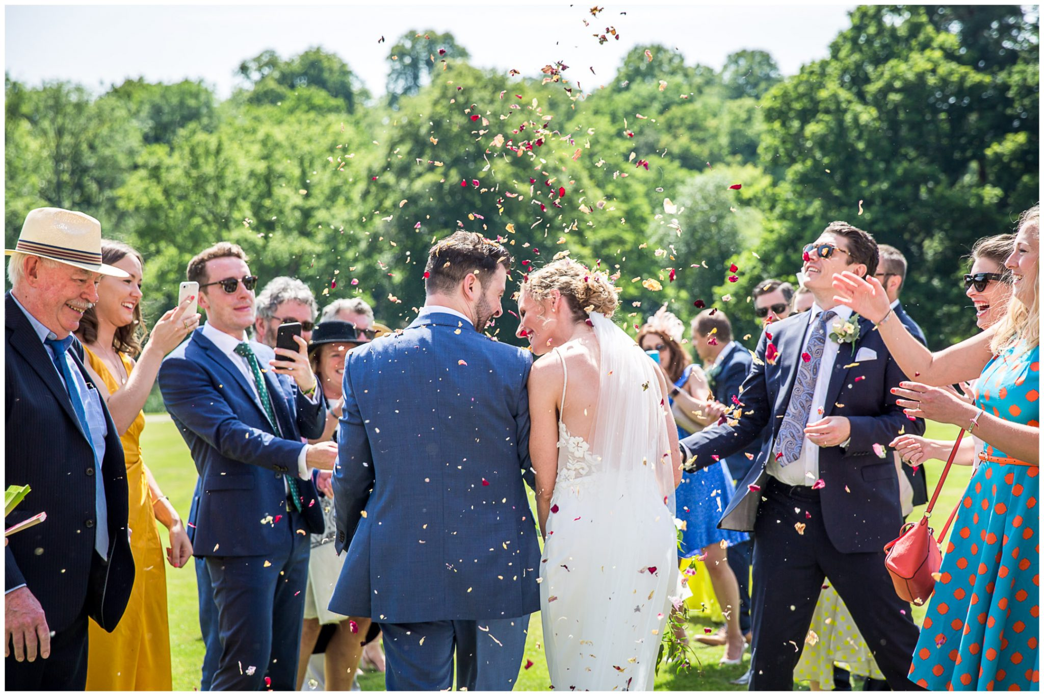 Wedding guests throw confetti over the couple