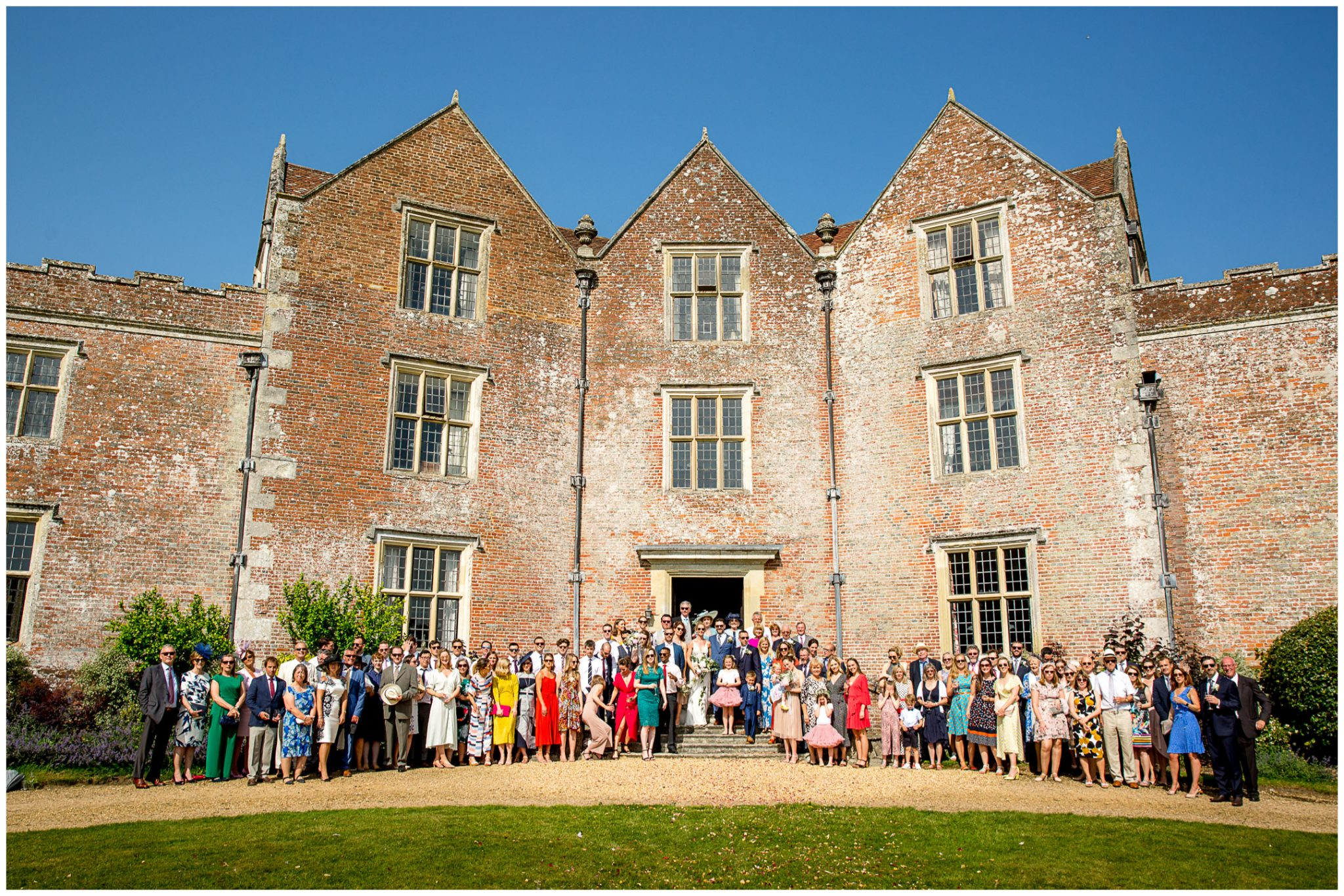 A large group photo of everyone outside the Redlynch wedding venue in the sunshine