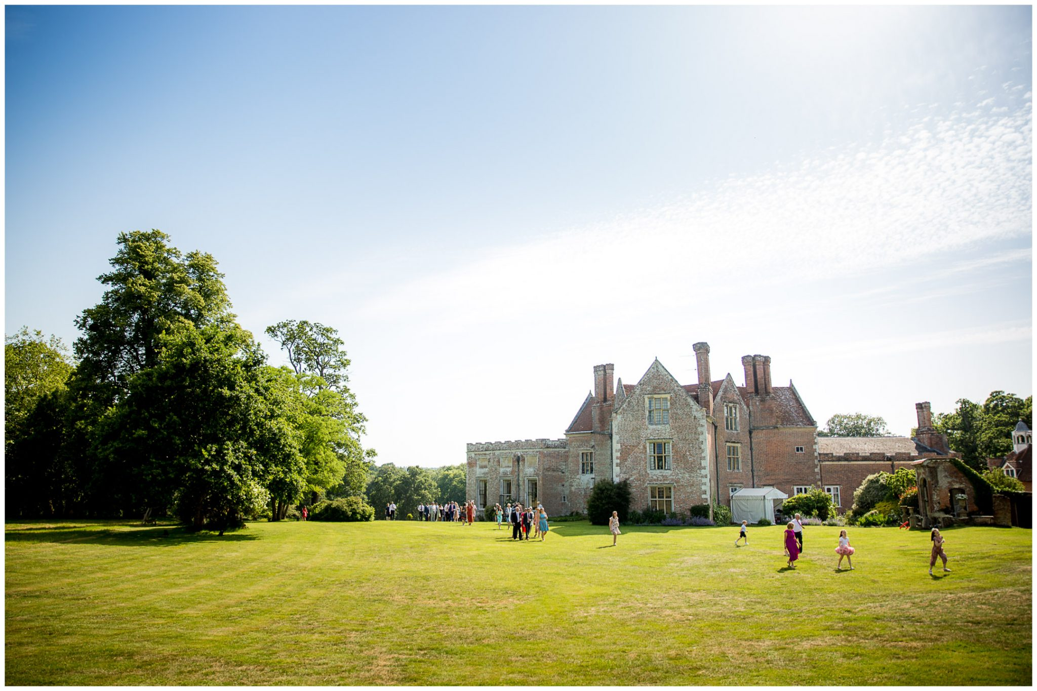 View of the rear of the manor house as guests make their way acrosss the lawns to the marquee for the wedding breakfast