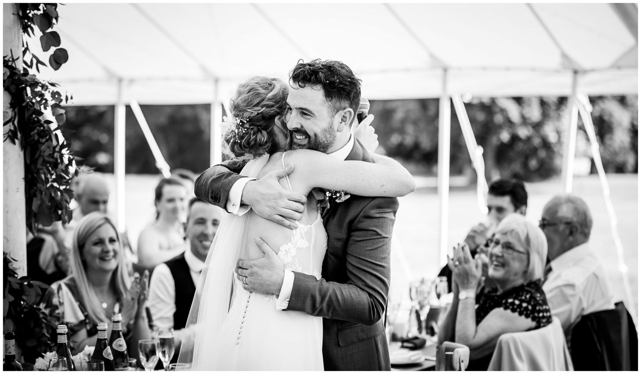 Bride and groom hug black and white candid photograph
