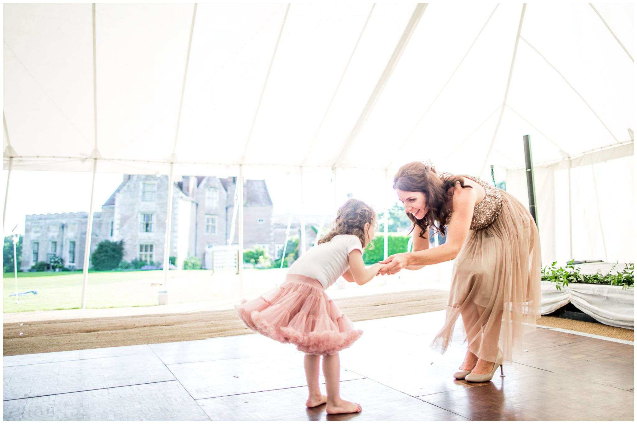 A bridesmaid dances with her daughter during the reception