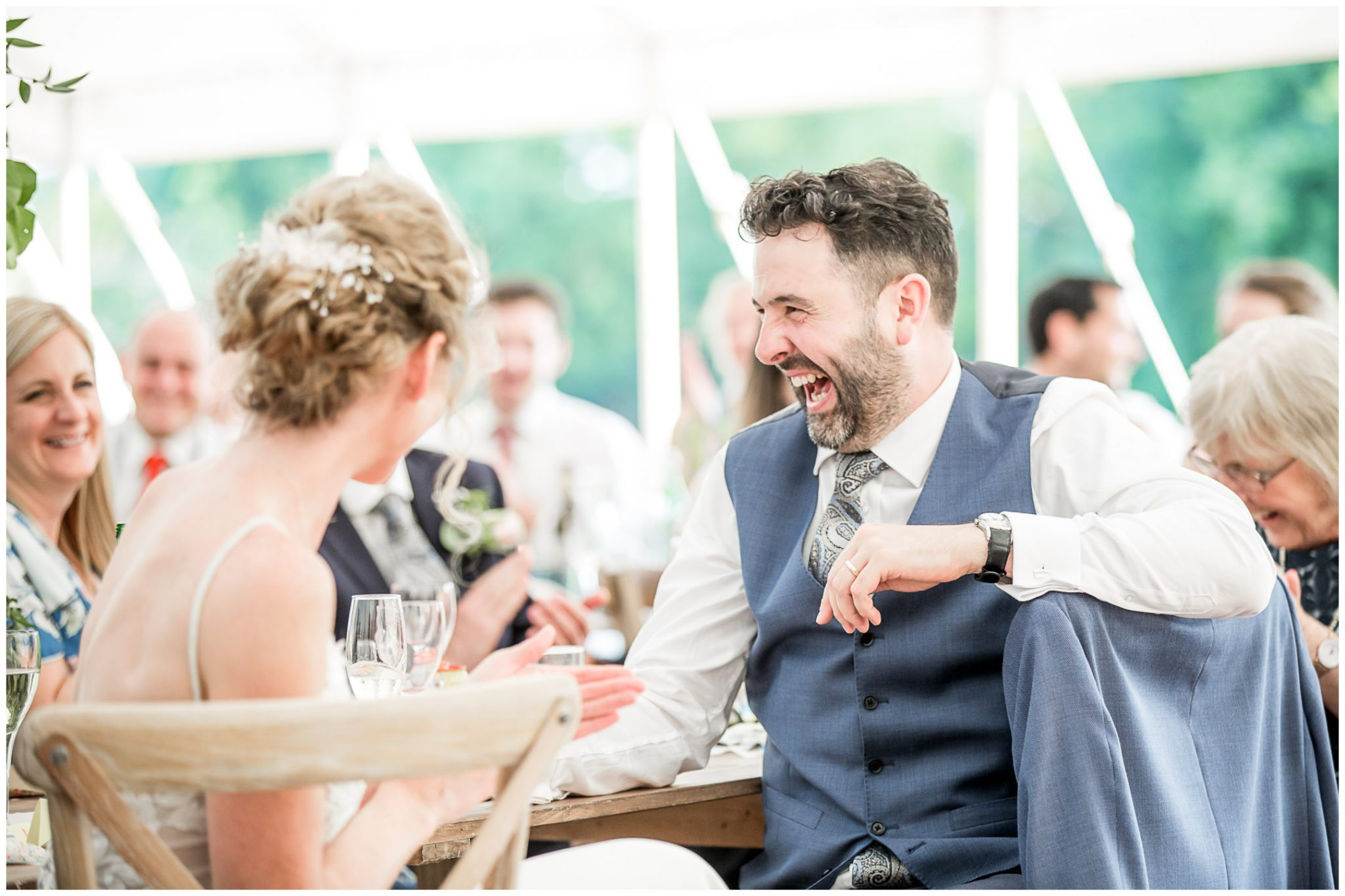 Groom laughing at the best man's speech